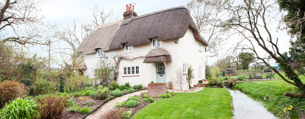 Thatch Cottage with Storm Evolution Windows โดย ROCOCO ชนบทฝรั่ง