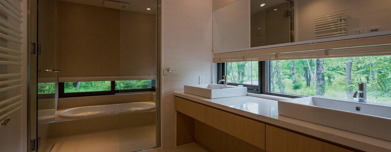 斜面を受け止める家: 株式会社sum designが手掛けた浴室です。