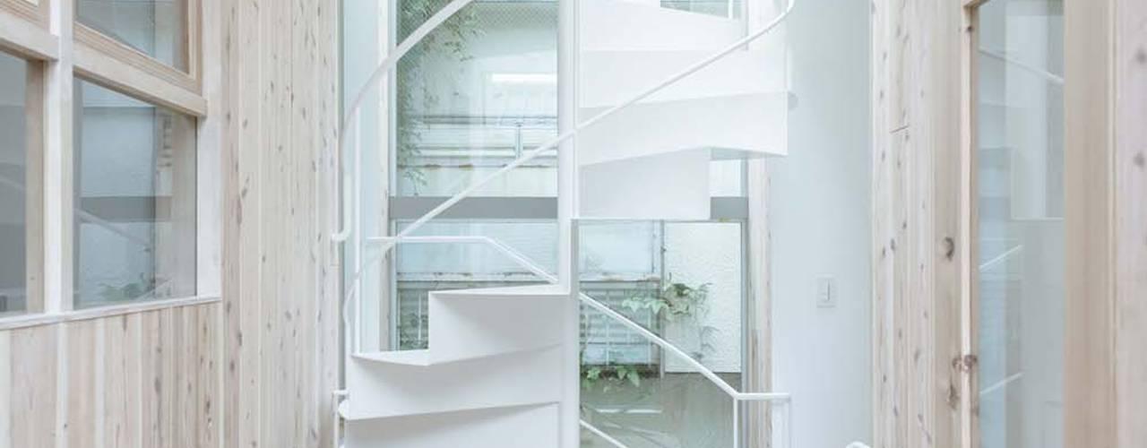 各部屋をつなぐ吹抜と螺旋階段: ディンプル建築設計事務所が手掛けた廊下 & 玄関です。