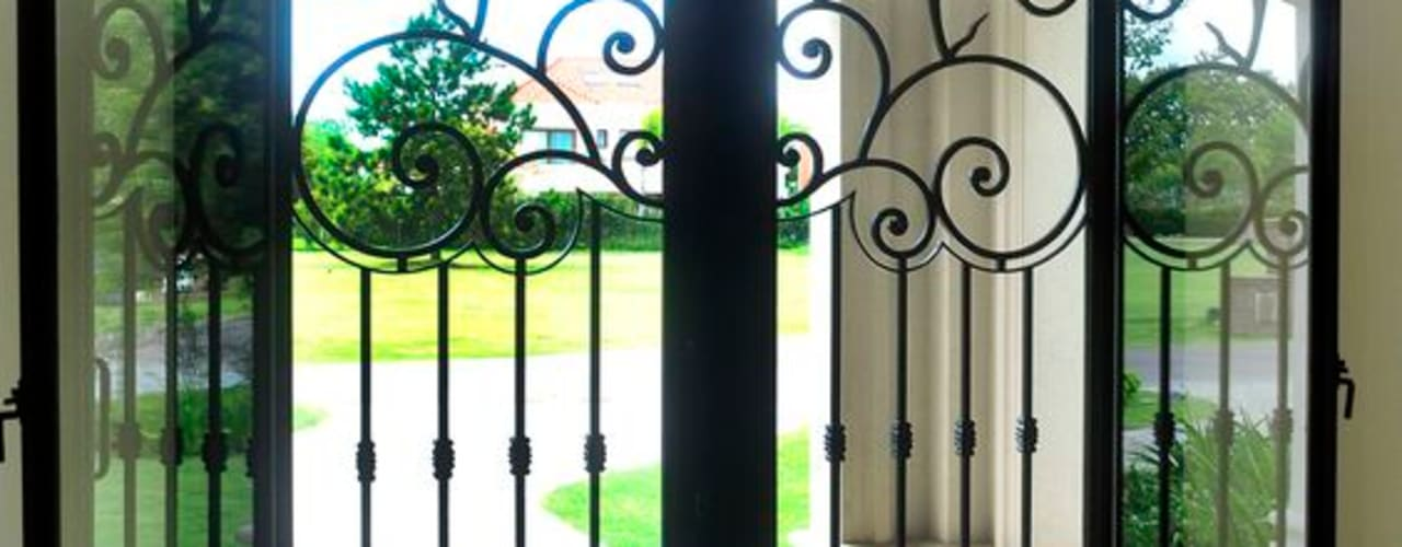 Puerta de entrada de hierro forjado: Ventanas de estilo  por DEL HIERRO DESIGN