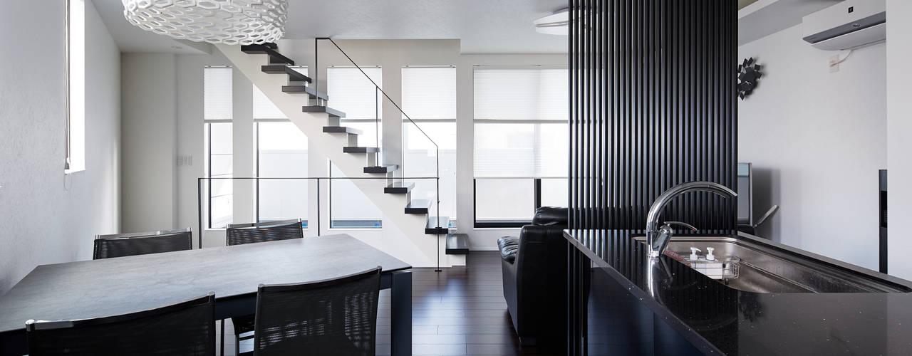 3角敷地に3角な3階建の家: 一級建築士事務所 株式会社KADeLが手掛けたリビングです。