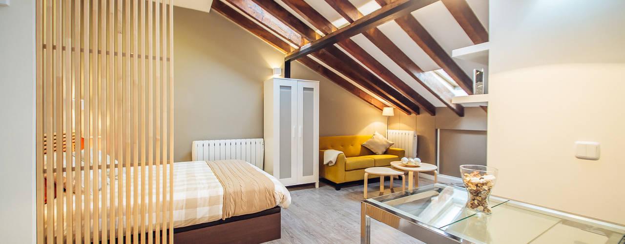 Reforma de vivienda abuhardillada en Madrid Centro.: Salones de estilo  de Arkin