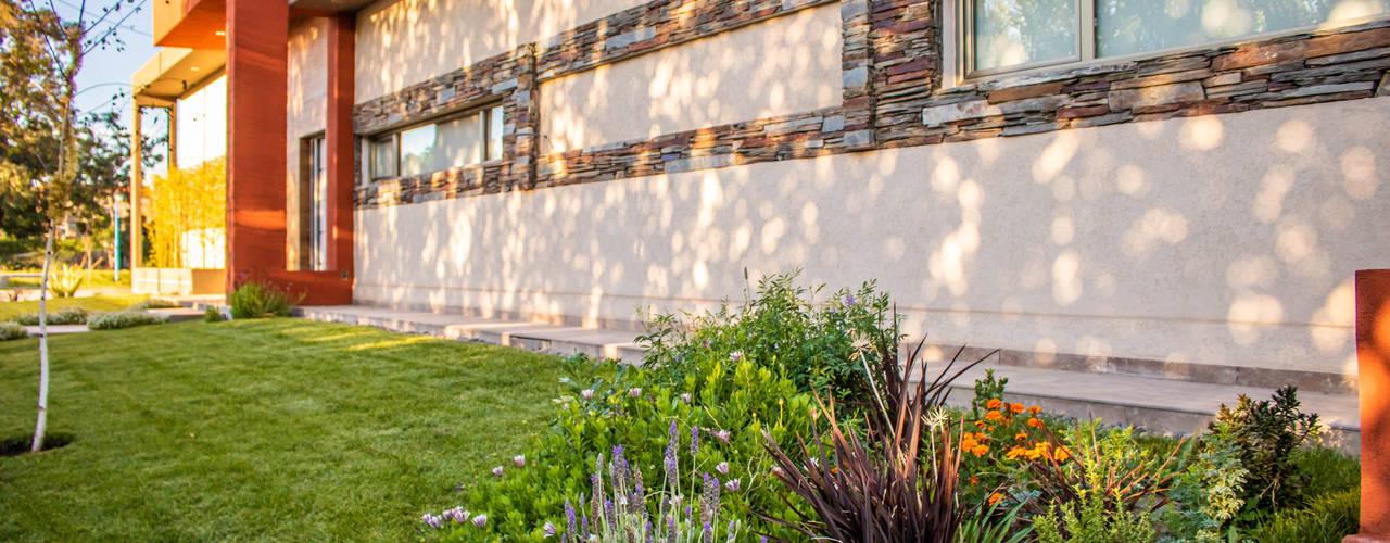 REFORMA DE FACHADA, PARQUE E INTERIORES Aida tropeano& Asociados Casas modernas: Ideas, imágenes y decoración Piedra Ámbar/Dorado