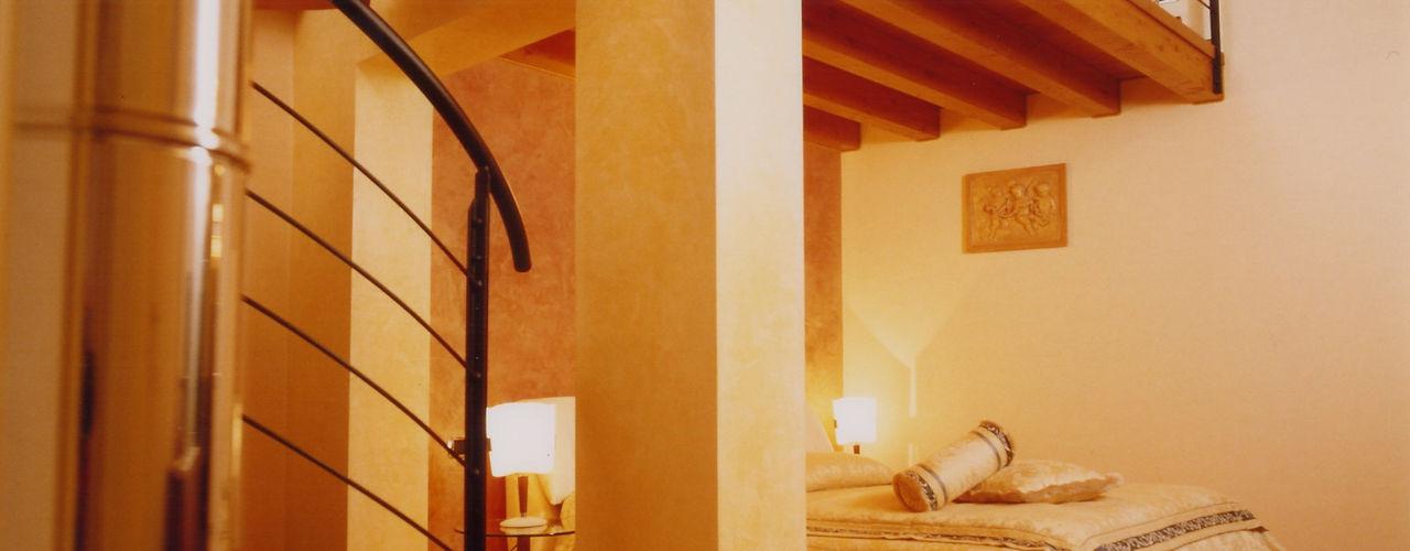 La scala come anima dell'abitazione STUDIO ARCHITETTURA SPINONI ROBERTO Camera da letto moderna Legno massello Giallo