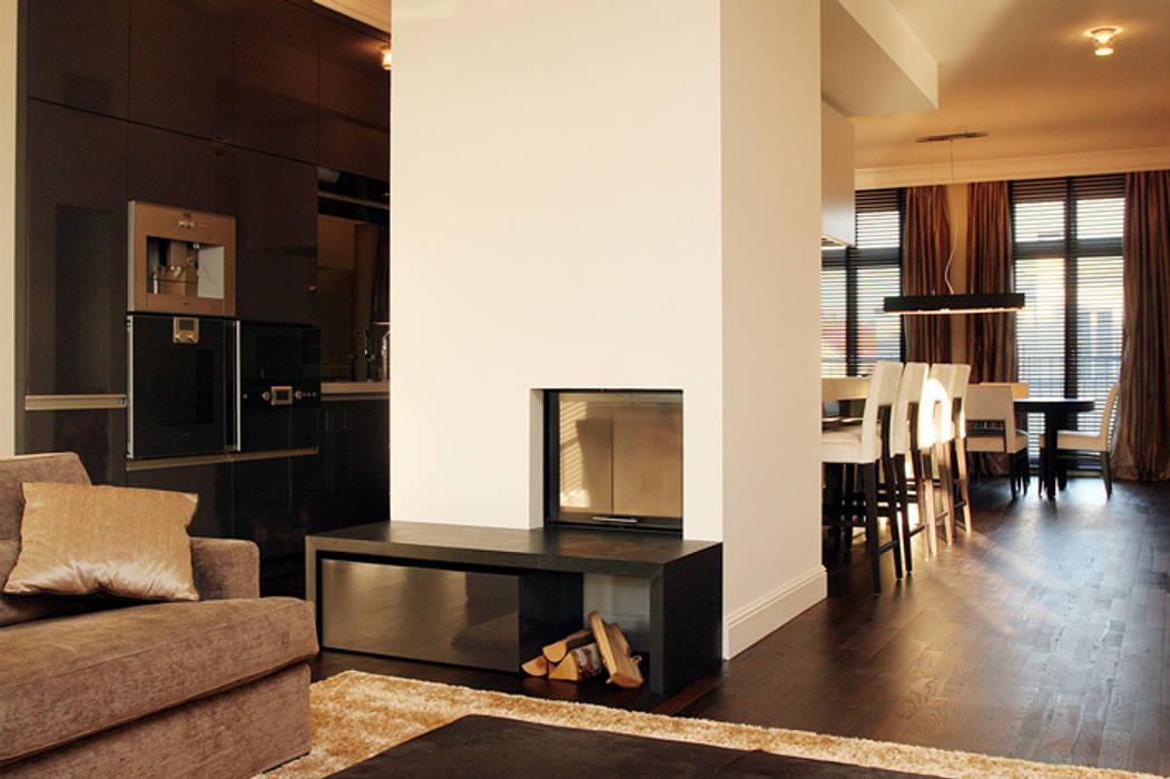 Wohnzimmer mit Kamin und offener Küche:  Wohnzimmer von Atelier Schöngestalt
