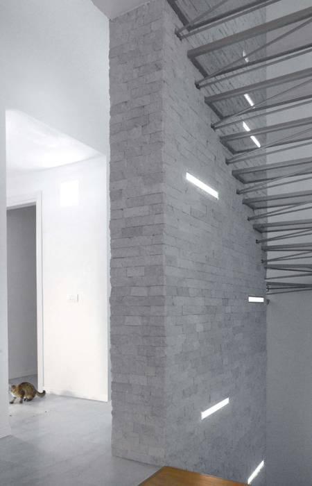 Setto portante centrale rivestito in pietra e completato da corpi illuminanti: Ingresso & Corridoio in stile  di boschi + serboli architetti associati, Moderno