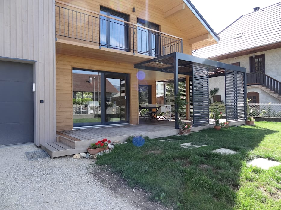 Vue de la façade principale et de la terrasse ombragée Maisons modernes par Tangentes Architectes Moderne