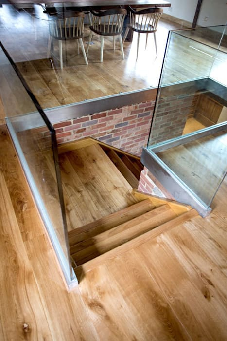 Open plan Living room with oak flooring and oak stairs:  Living room by Fine Oak Flooring Ltd.