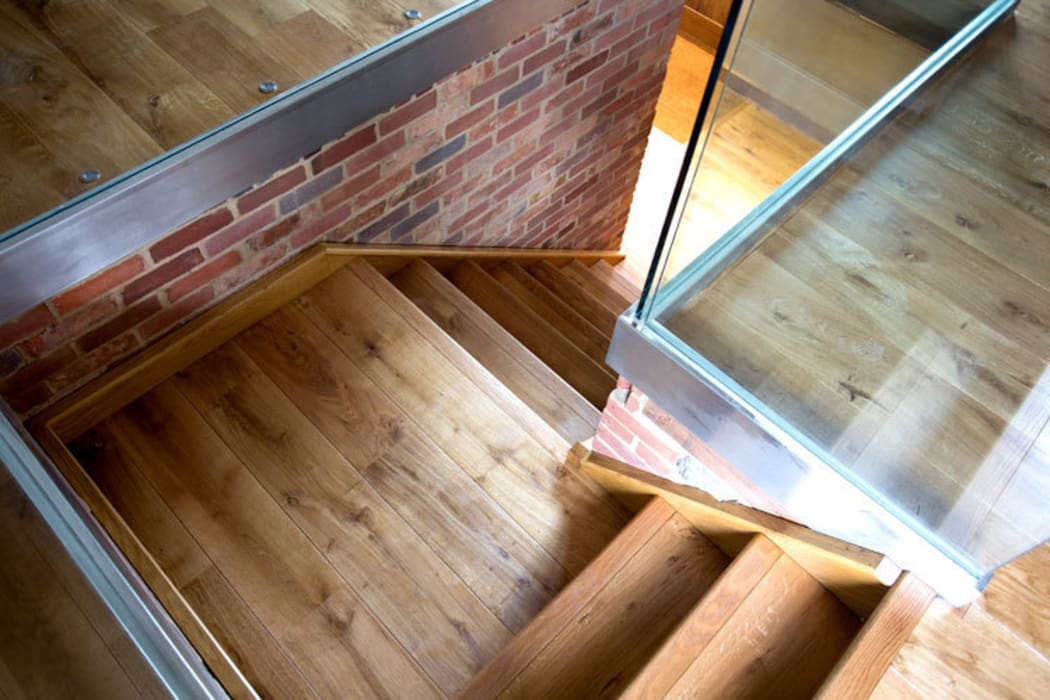 Oak stairs in the rustic barn:  Living room by Fine Oak Flooring Ltd.