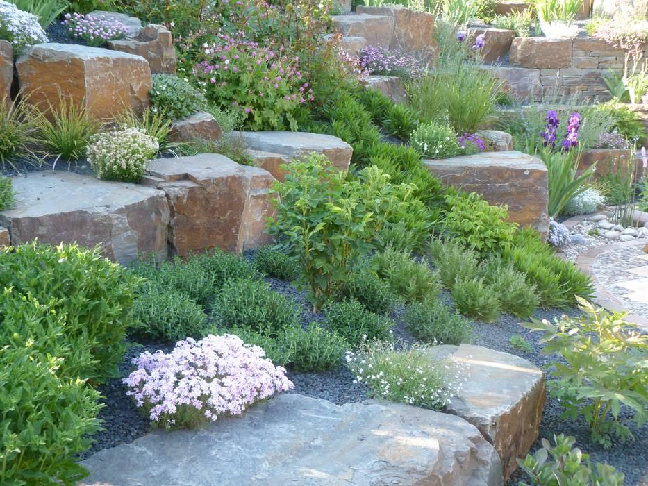 Mit Natursteinblöcken abgefangene Böschung von Gärten für Auge und Seele Mediterran