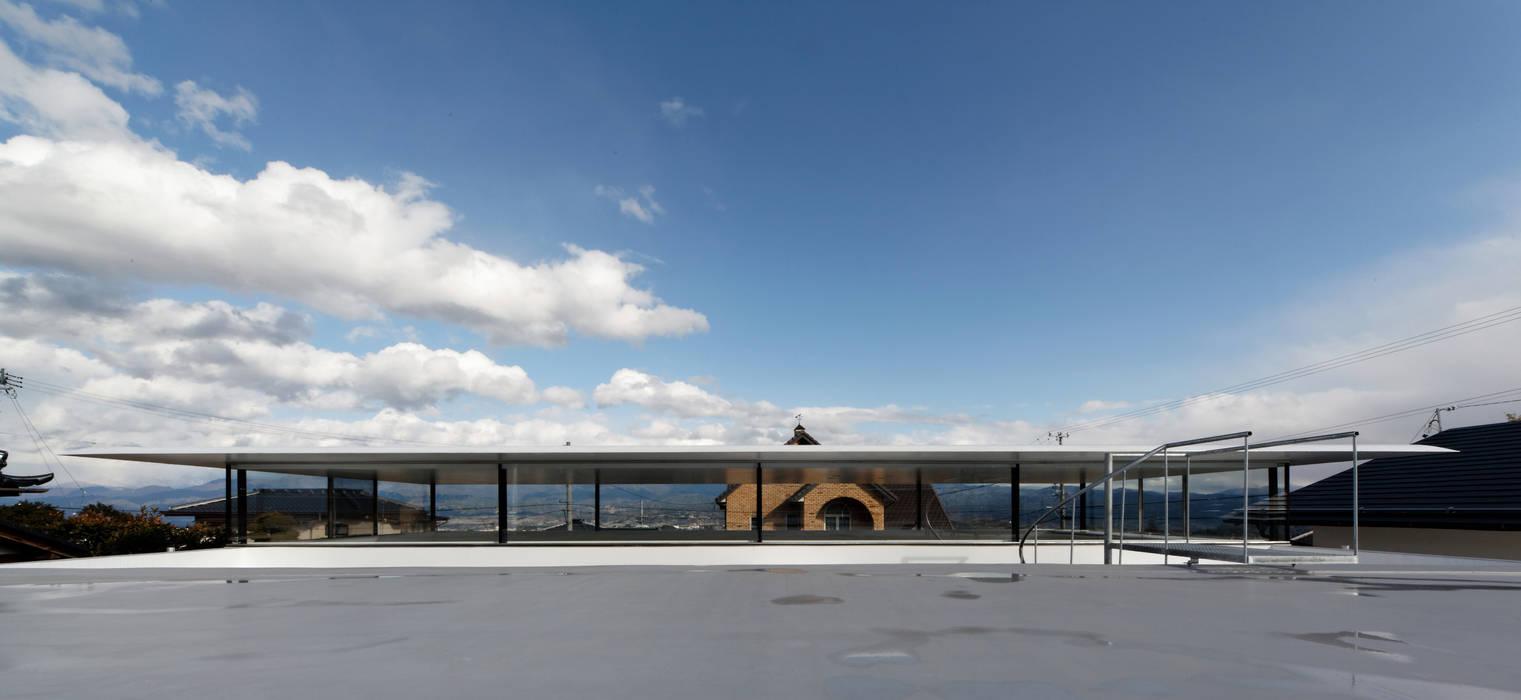特徴的な屋根と背後の山並みとの対比: TNdesign一級建築士事務所が手掛けた家です。