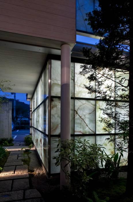 玄関からアプローチ、ガレージの壁を見る: 有限会社加々美明建築設計室が手掛けたガレージです。,オリジナル
