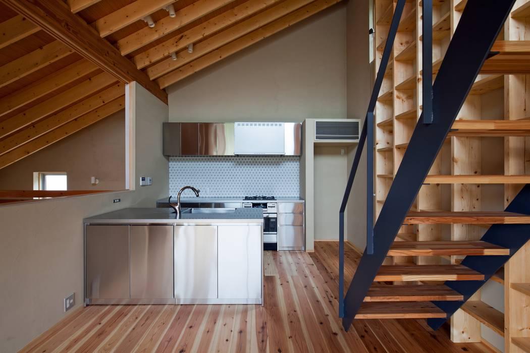 「ごはんができたよ」って吹抜けから家族に声をかける司令塔キッチン クラシックデザインの キッチン の 根岸達己建築室 クラシック 無垢材 多色