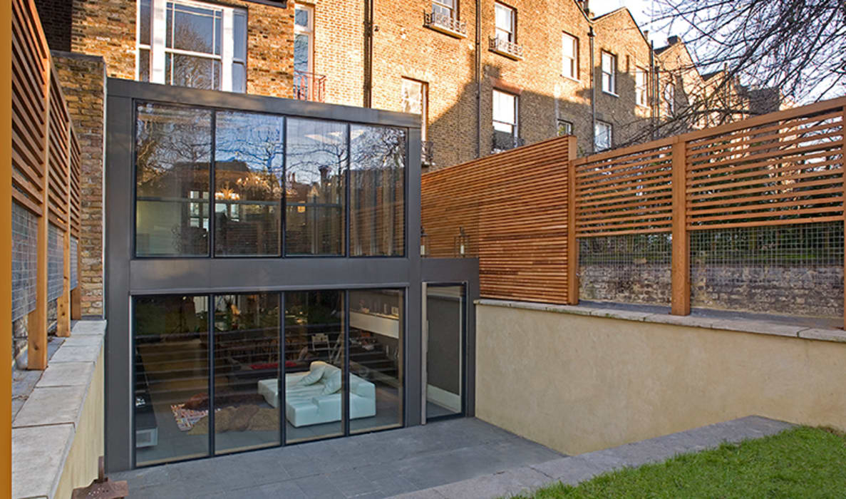 The minimal rear extension and sunken terrace:  Houses by Hale Brown Architects Ltd,