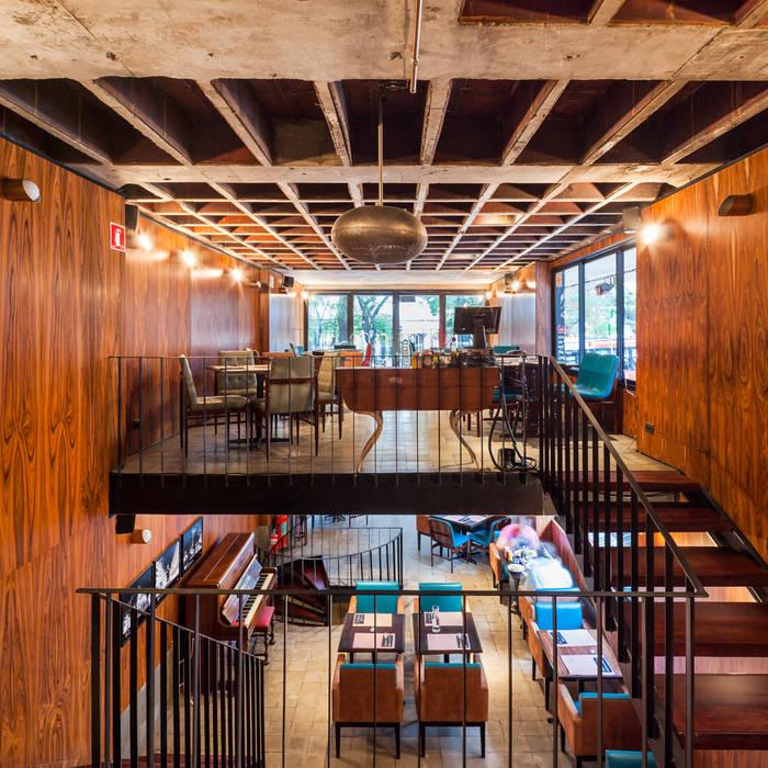 Vista do mezanino para o térreo e pavimento superior: Espaços gastronômicos  por MM18 Arquitetura