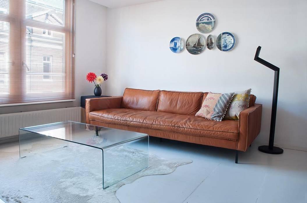 cognackleurige bank en kunst aan de muur Moderne woonkamers van IJzersterk interieurontwerp Modern