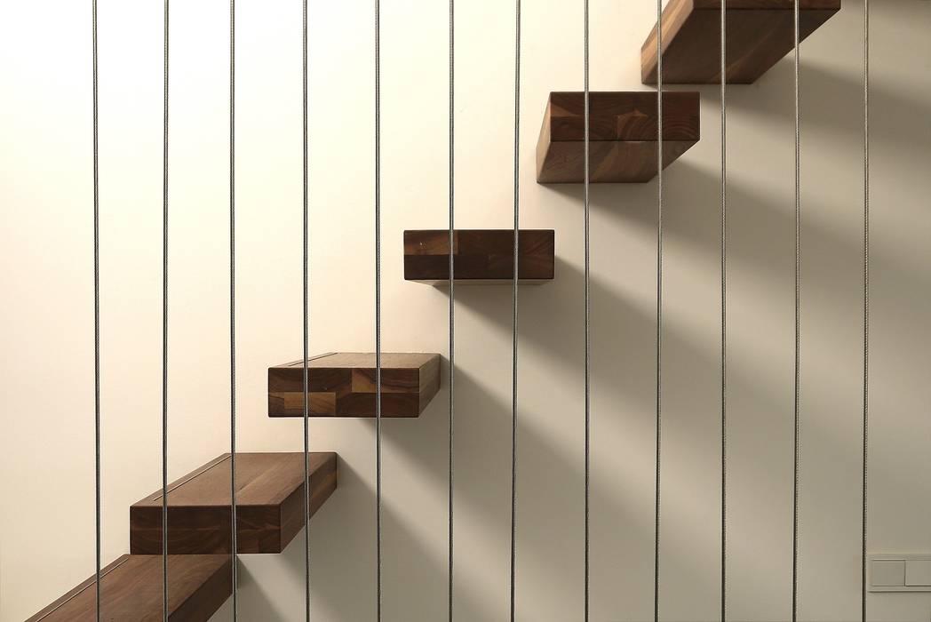 Zwevende trap met notenhouten treden Moderne gangen, hallen & trappenhuizen van Leonardus interieurarchitect Modern
