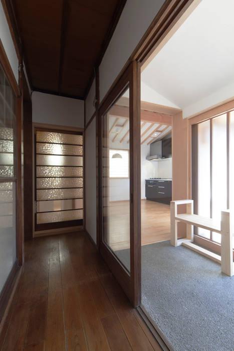 古き廊下より新たな増築部を見る: 結人建築設計事務所が手掛けた廊下 & 玄関です。