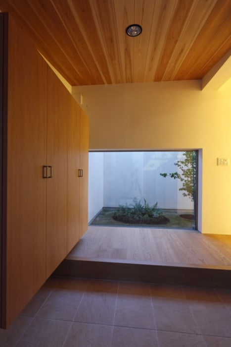 キッチンの家 玄関夕景: アーキシップス古前建築設計事務所が手掛けた壁です。