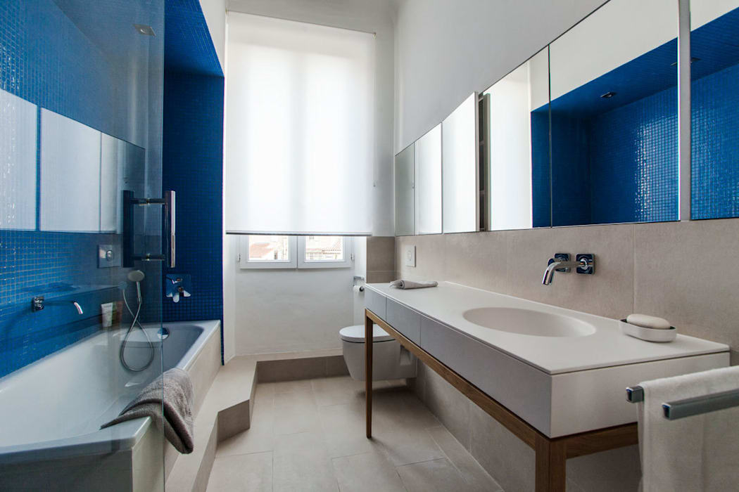 Le revêtement en carrelage beige de la marche, du sol et du mur permet d'unifier l'espace de manière douce. Charlotte Raynaud Studio Salle de bain minimaliste