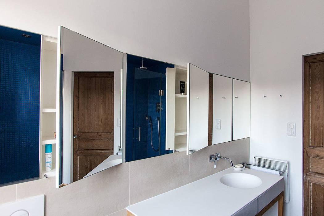 Des rangements se cachent derrière les portes-miroirs Charlotte Raynaud Studio Salle de bainRangements
