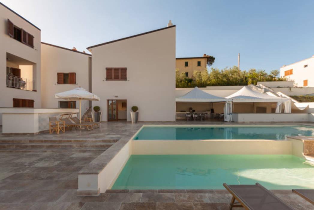 Piscina in travertino in resort nella campagna toscana: Hotel in stile  di Pietre di Rapolano