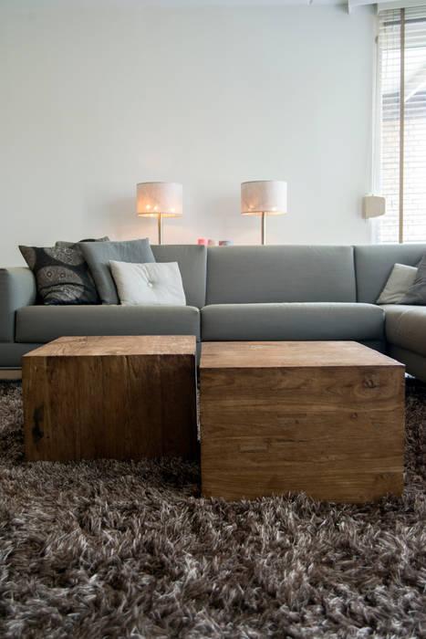 Moderne bank in combinatie met grove houten salontafels:  Woonkamer door Hemels Wonen interieuradvies , Modern