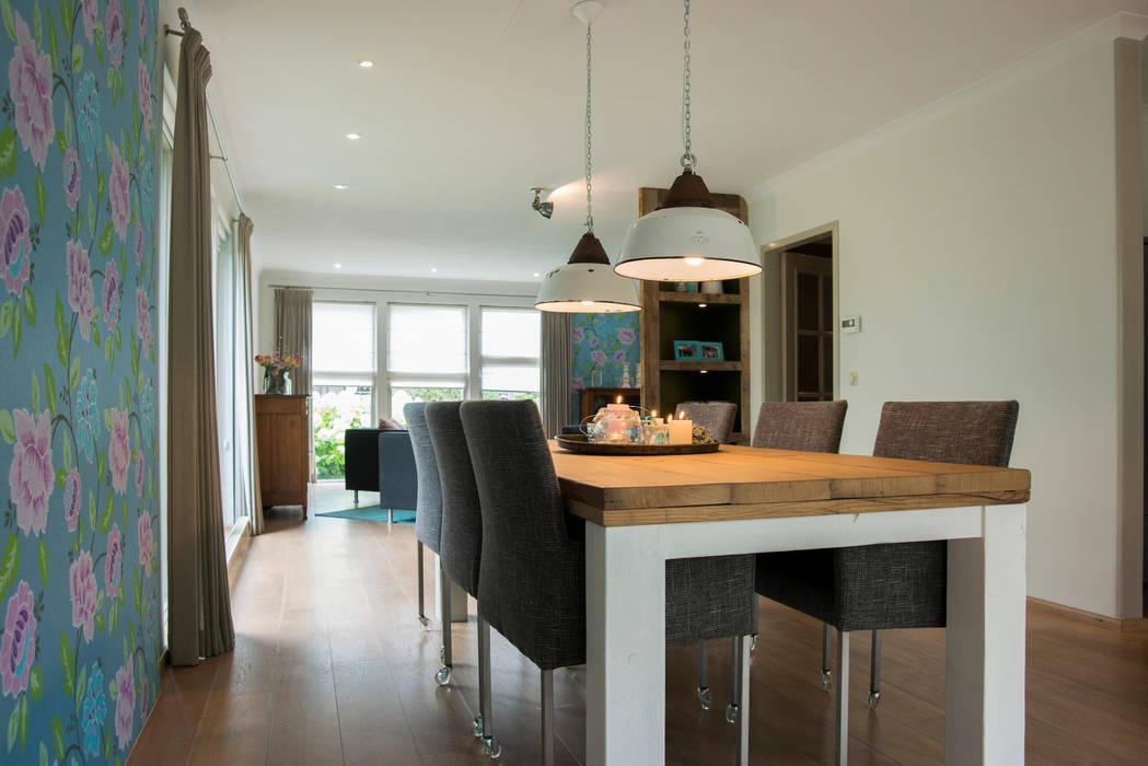De eetkamertafel met moderne stoelen en antieke lampen:  Eetkamer door Hemels Wonen interieuradvies