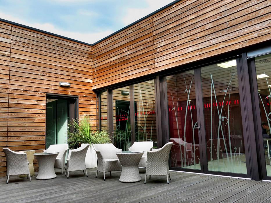 Le patio au premier étage: Hôpitaux de style  par AGENCE D'ARCHITECTURE BRAYER-HUGON