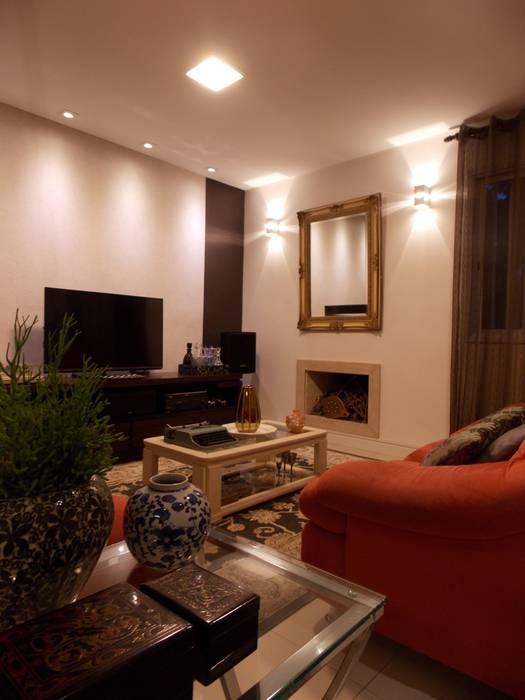 Sala aconchegante com sofás vermelhos: Salas de estar  por Lúcia Vale Interiores,Eclético