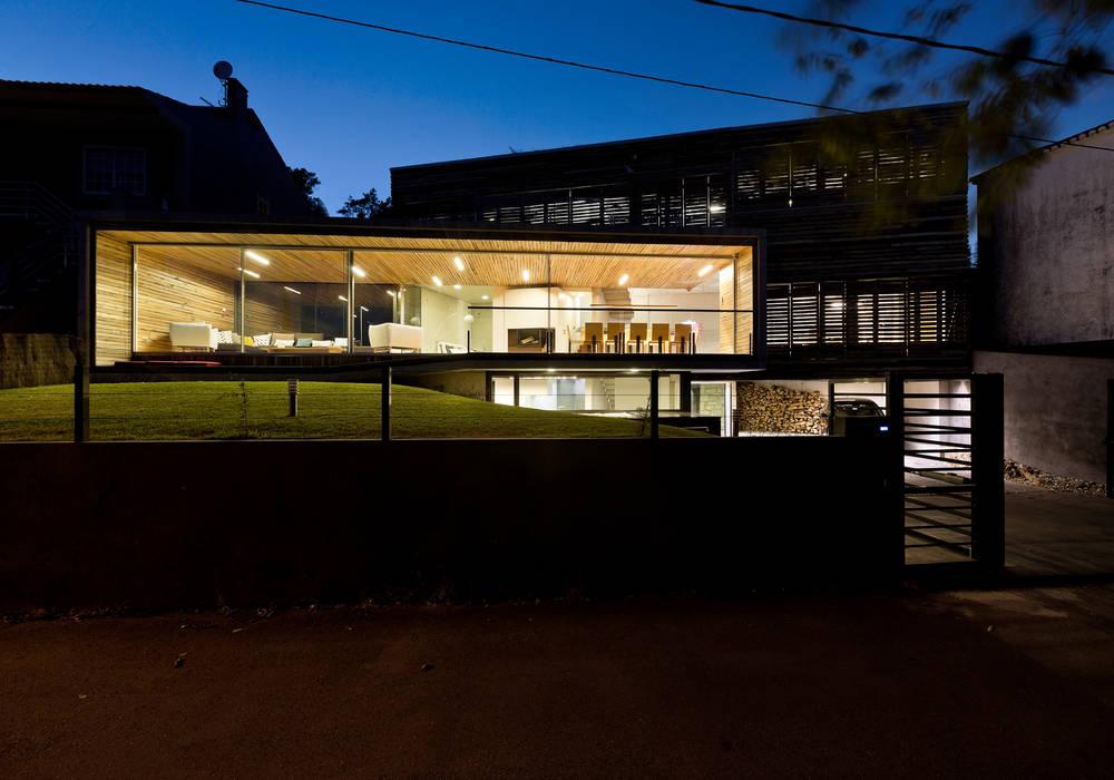 dezanove house designed by iñaki leite - front elevation at twilight Inaki Leite Design Ltd. Salones de estilo moderno