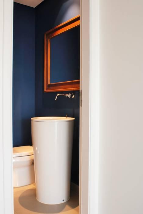 Lavabo com paredes azuis : Banheiros  por Gisele Emery Arquitetura
