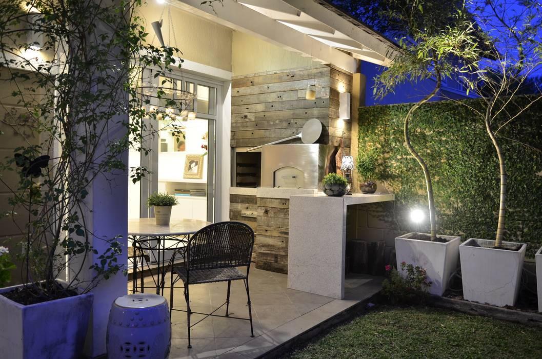 Elegante casa em condomínio: Terraços  por Tania Bertolucci  de Souza  |  Arquitetos Associados,