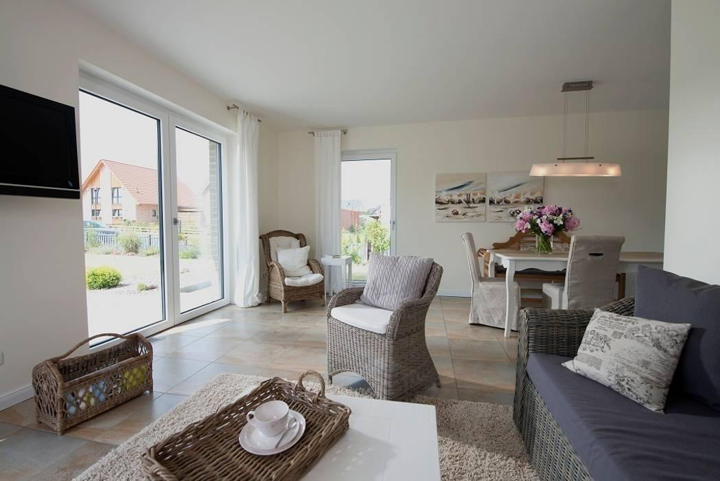 Der luftig gestaltete Wohnbereich mit den bodentiefen Fenstern bildet den Lebensmittelpunkt des Hauses. Klassische Wohnzimmer von Heinz von Heiden GmbH Massivhäuser Klassisch