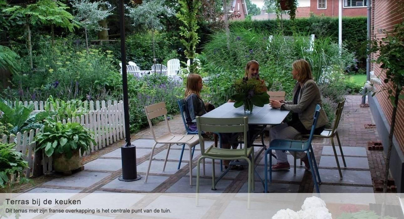 Heerlijk uitzicht op moestuin & terras, vanuit de overkapping bij de openslaande deuren van de keuken. Moderne tuinen van Groene Kikker Tuinontwerp Modern