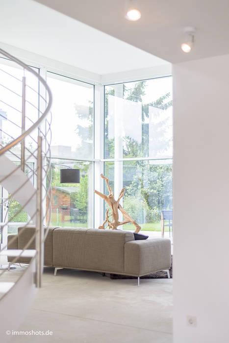 Blick von Entree in die Wohnhalle: moderner Wintergarten von Immotionelles
