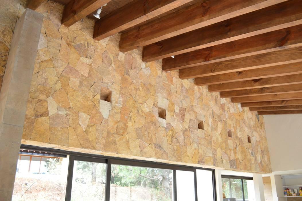 Muro forrado con Laja de Oro Viejo. Detalle de iluminacion indirecta. Paredes y pisos de estilo moderno de Revah Arqs Moderno