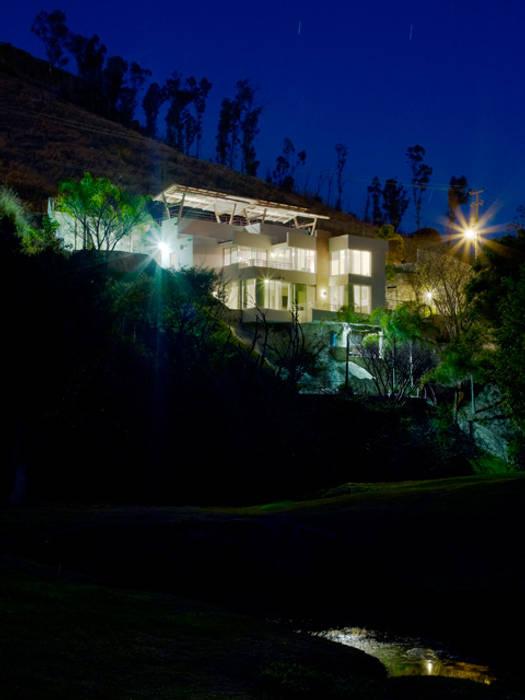 fachada posterior nocturna Casas modernas de Excelencia en Diseño Moderno Ladrillos