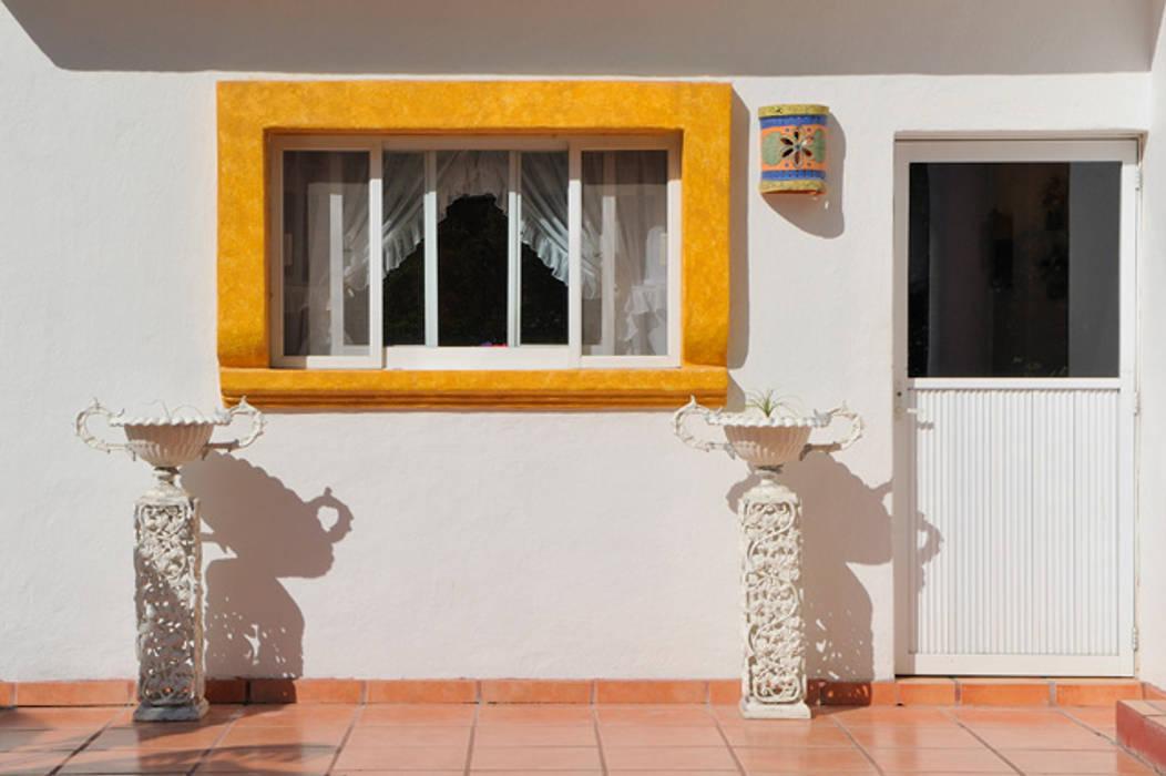 ventana al jardin: Ventanas de estilo  por Excelencia en Diseño