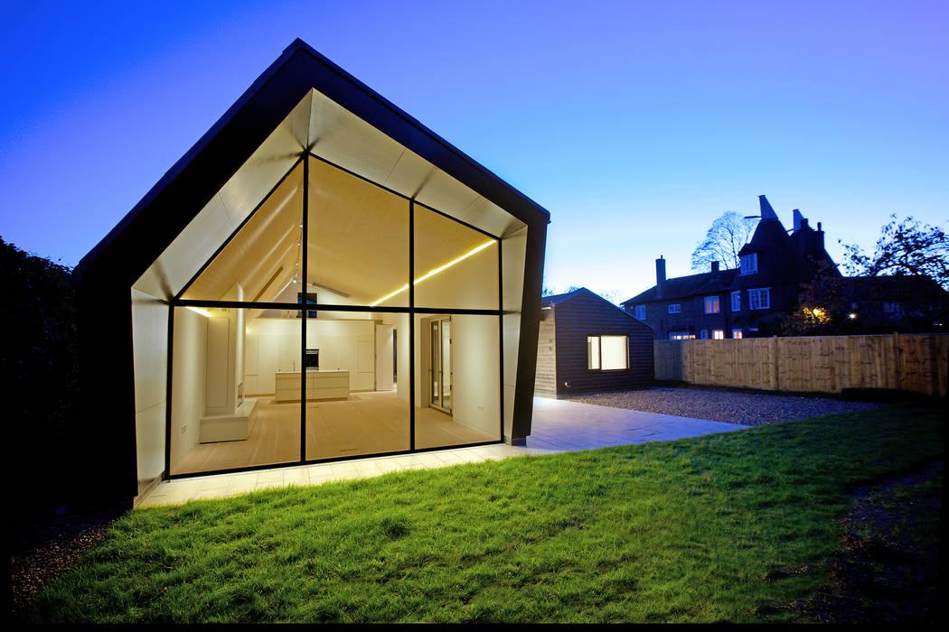 Rear elevation of Bourne Lane eco-house in Kent at twilight من Nash Baker Architects Ltd حداثي زجاج