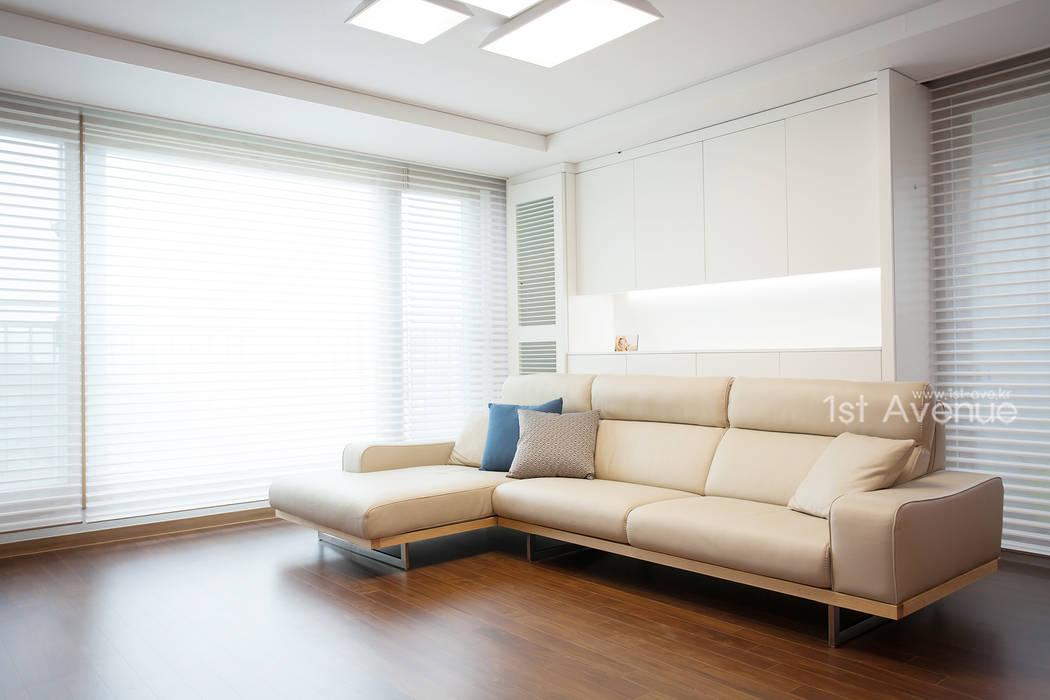 시원한 블루가 포인트 되어주는 인테리어: 퍼스트애비뉴의  거실