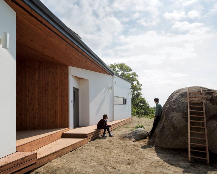 바위를 낀 대청: B.U.S Architecture의  주택