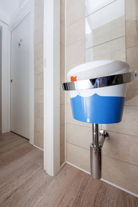 Un piccolo lavabo dalla curiosa forma di secchiello da spiaggia: Cliniche in stile  di STUDIO PAOLA FAVRETTO SAGL - INTERIOR DESIGNER