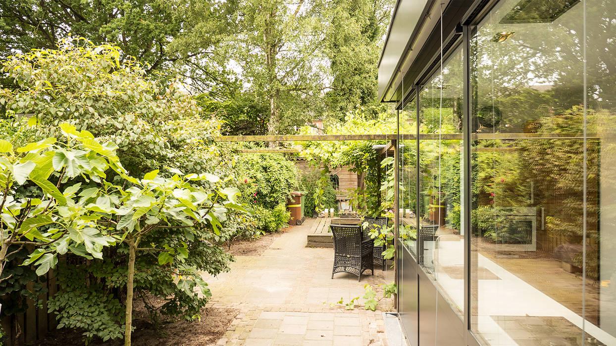 Luxe smalle aanbouw met keuken pal op het zuiden, aluminium schuifpui en lamellen zonwering Joep van Os Architectenbureau Moderne tuinen