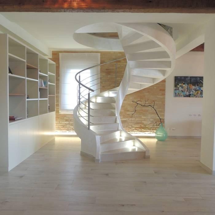 Scala elicoidale moderna in cemento con pedate in marmo e balaustra in acciaio: Ingresso & Corridoio in stile  di Nadia Moretti, Moderno