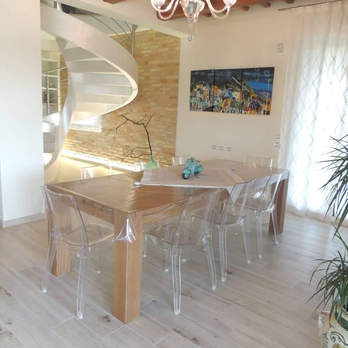 Sala da pranzo con tavolo in rovere e sedie moderne in policarbonato ...