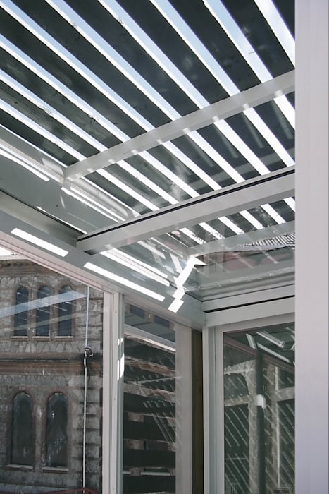 dettaglio del doppio scorrimento dei pannelli del patio: Terrazza in stile  di Altro_Studio