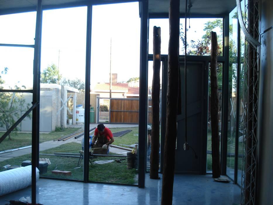 los postes de quebracho: Estudios y oficinas de estilo moderno por CRISTINA FORNO