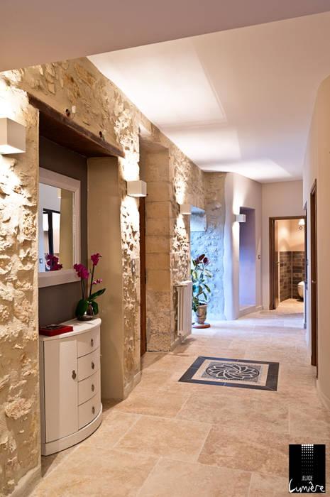 Couloir avec mur en pierre: Couloir et hall d'entrée de style  par Jeux de Lumière