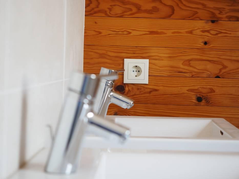 Cerâmico e madeira na casa de banho.: Casas de banho  por Lethes House,